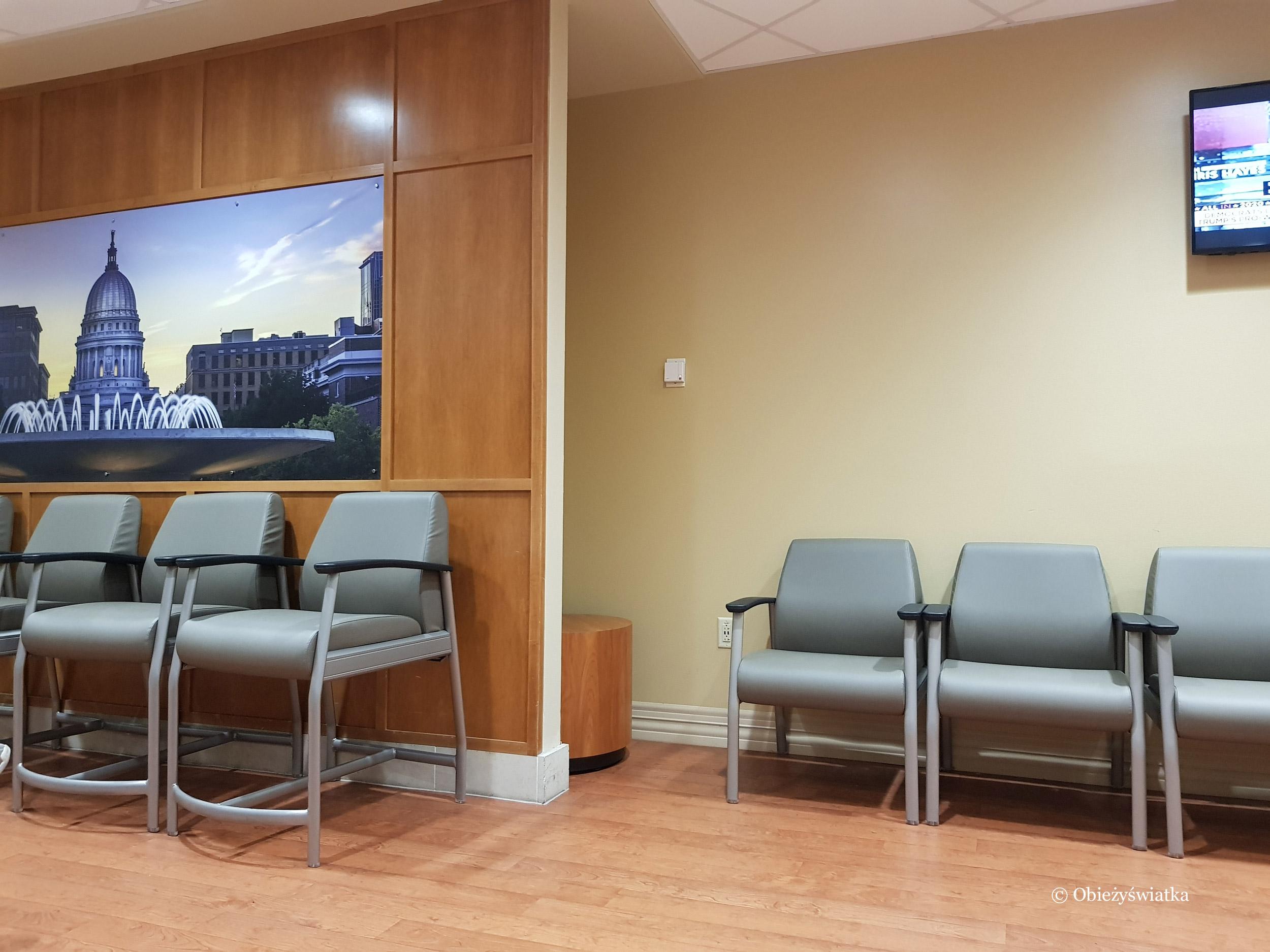 Poczekalnia na ostrym dyżurze z krzesłami o różnej szerokości siedzeń, USA